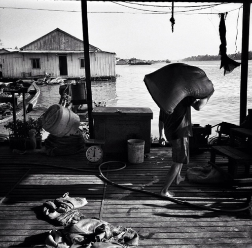 "David Guttenfelder, ""A Vietnamese man who raises catfish under his floating home carries a sack of fish food in the Mekong Delta town of Chau Doc"" 2014"