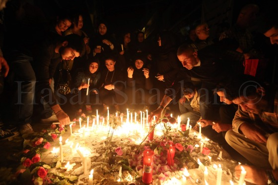 people light candles during a vigil at the site of the two explosions. November 13, 2015. REUTERS/Hasan Shaaban
