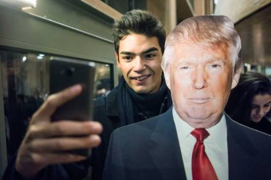 R. Kalvar, France. Paris.  Following the American elections at the Carré du Temple. Posing for a selfie with Trump. 2016